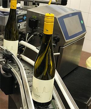 Nach der Befüllung werden die Flaschen mit Etiketten versehen und anschließend codiert.