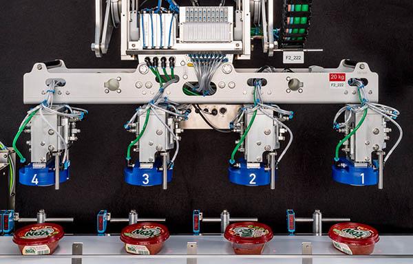 Jedes Werkzeug des sogenannten Springsaugers fährt einzeln in flexiblem Takt nach unten und nimmt einen der Becher vom Band auf. Sind alle vier Sauger belegt, setzt der Roboterarm die Becher in die Ausrichtstation um.