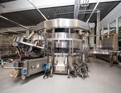 Ein Servomotor dreht die Flaschen, Linearmotoren drücken die Folie mithilfe von Schwämmen an die Behälter an
