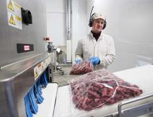 Die Beutelverpackungen mit Elchfleisch werden manuell auf die Zuführung gegeben