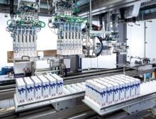 F2-Roboter übernehmen die befüllten und verschlossenen Geschenkpackungen aus dem Transmodul und setzen sie in die Verkaufskartons