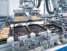 Frisch aus dem Backofen werden jeweils vier Kaffeekuchen leicht angehoben und von einem F2-Roboter auf das Auslaufband gesetzt